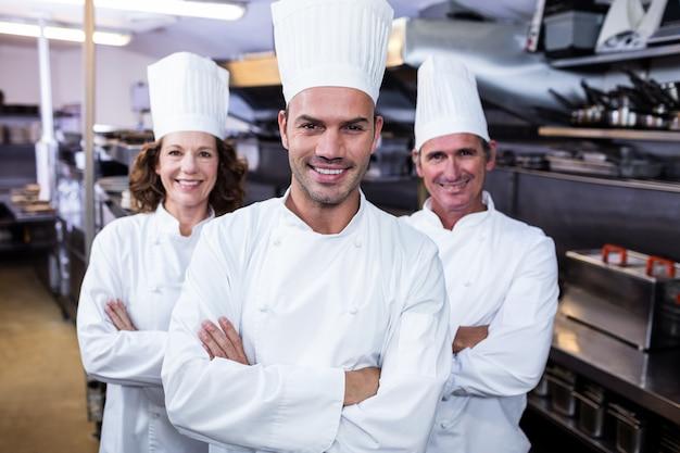 Drużyna szefów kuchni stoi z rękami krzyżować