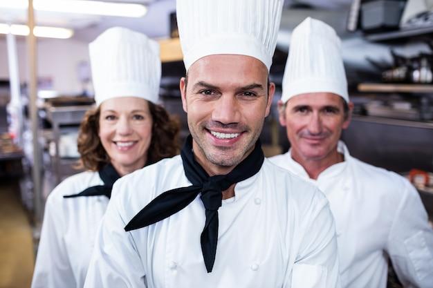 Drużyna szefowie kuchni ono uśmiecha się w handlowej kuchni