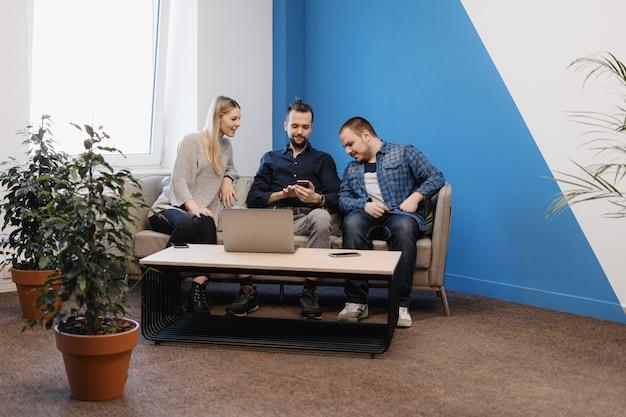 Drużyna trzy osoby pracuje na laptopie w biurze na kanapie