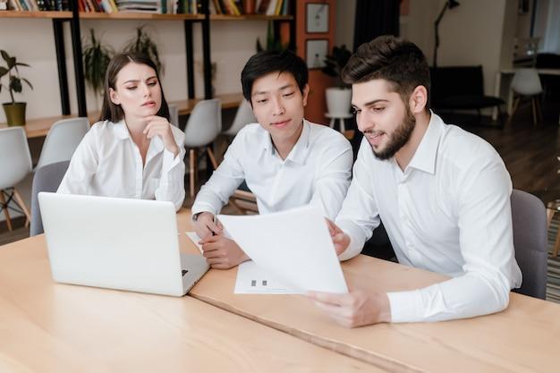 Drużyna urzędnicy siedzi przy biurka dyskutować z laptopem i dokumentami