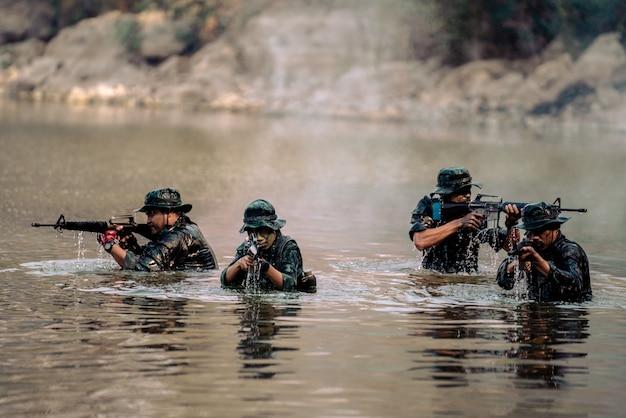 Drużyna żołnierzy biegnących w wodzie