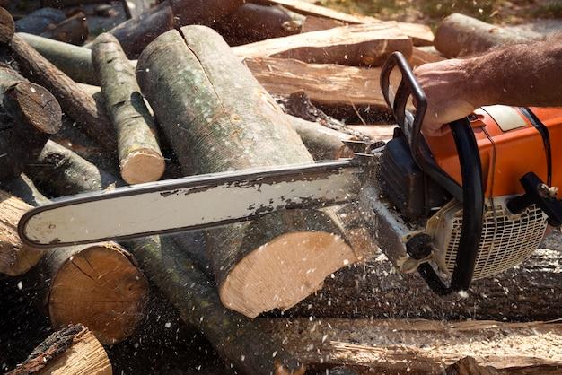 Drwal tnący drewno piłą łańcuchową