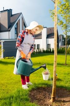 Drzewa i rośliny. przyjemna, miła kobieta dobrze czuje się podczas podlewania roślin