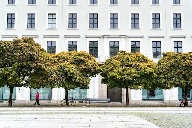 Drzewa przed nowoczesnym białym apartamentowcem w świetle słonecznym w ciągu dnia