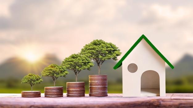 Drzewa rosnące na ułożonych w stos srebrnych monetach i modele domów na drewnianych stołach