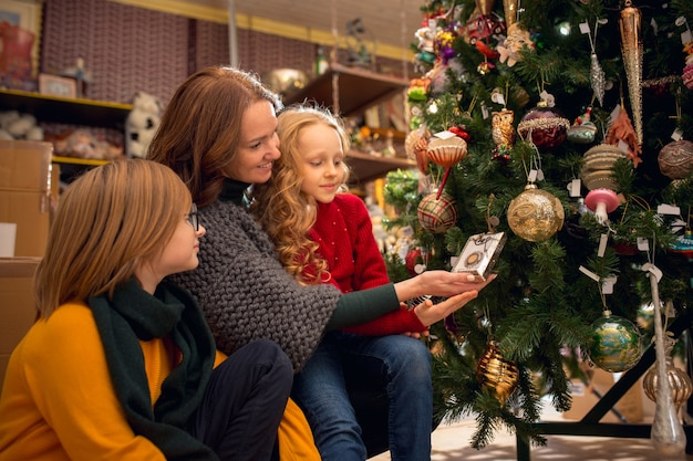Drzewko świąteczne. uśmiechnięta rodzina, mama i dzieci szukające dekoracji do domu i świątecznych prezentów w sklepie gospodarstwa domowego. stylowe retro rzeczy na pozdrowienia lub projekt. remont wnętrz, świętowanie czasu.