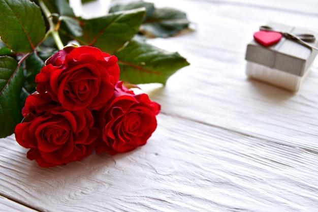 Drzewne czerwone róże i prezenta pudełko na biały drewnianym. koncepcja walentynki