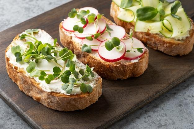 Drzewne kanapki z świeżymi mikrogreen rzodkiewkami i kremowym serem na szarym tle. ścieśniać.