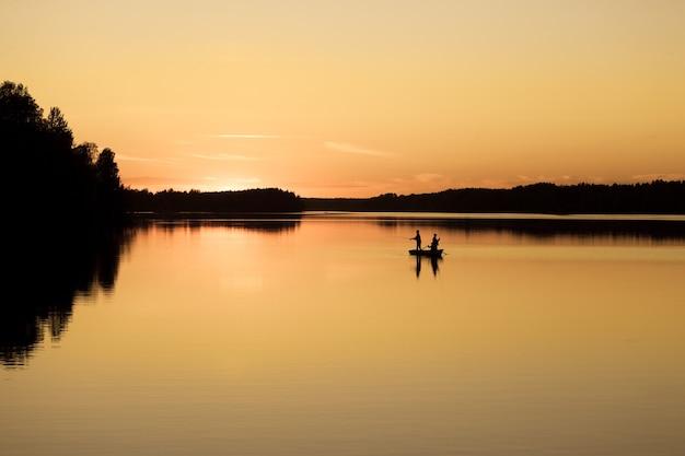 Drzewni mężczyźni łowiący ryby w łodzi na rzece vuoksa