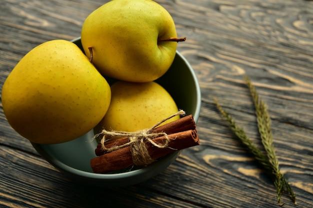 Drzewni żółci jabłka i cynamonowi kije w pucharze na ciemnym drewnianym tle. widok z boku. martwa natura.