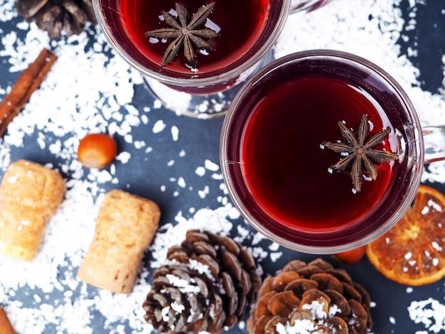 Drzewo mandarynki i gałązki z dwiema szklankami grzanego wina z pomarańczami i przyprawami.