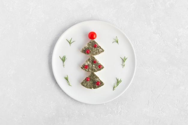 Drzewo noworoczne z sera i ozdobione czerwoną porzeczką i pomidorkami koktajlowymi, dekoracja stołu noworocznego, biały talerz, widok z góry