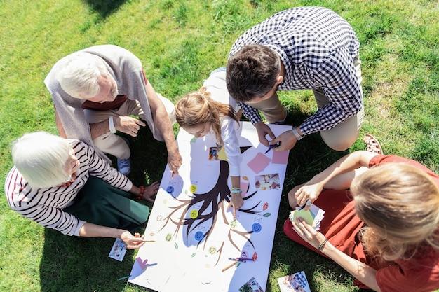 Drzewo rodzinne. wesoły dzieciak opierając się na trawie, wskazując na zdjęcie