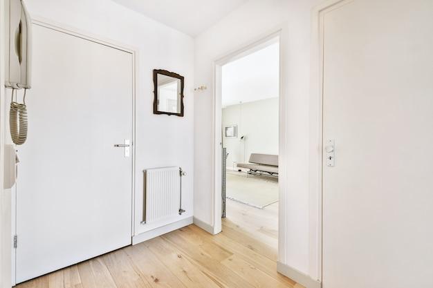 Drzwi otworzyły się z minimalistycznego stylu na jasny pokój z sofą w nowoczesnym mieszkaniu