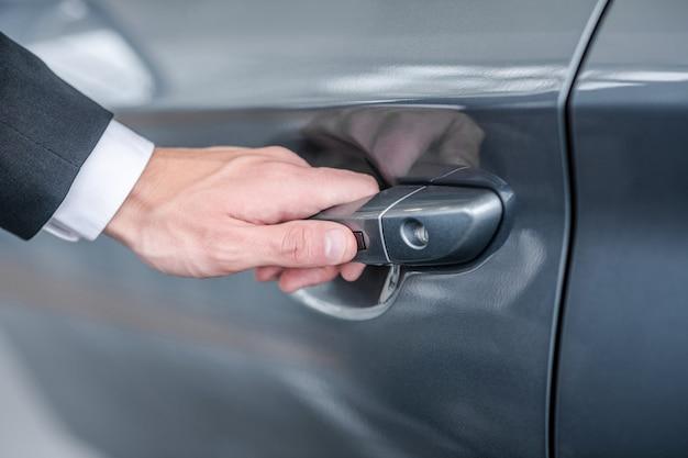 Drzwi samochodowe. ręka mężczyzny w garniturze otwierająca klamkę błyszczącego nowego samochodu, bez twarzy