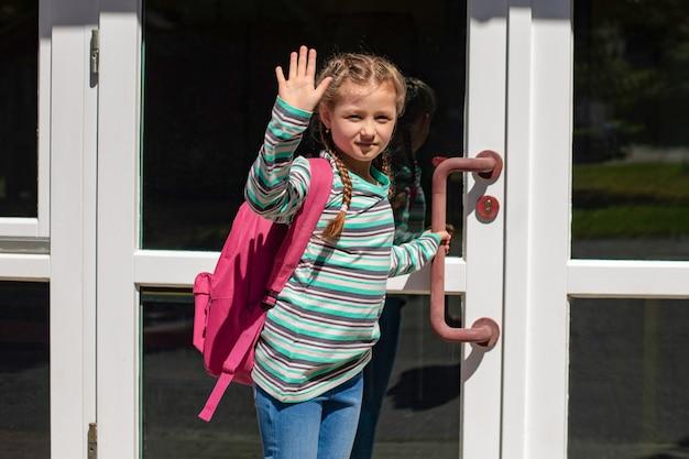 Drzwi szkoły otwiera dziewczyna z różową torbą