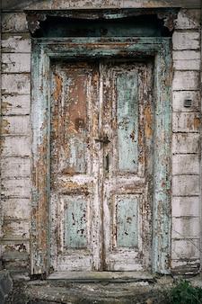 Drzwi w tradycyjnym starym drewnianym zaniechanym domu