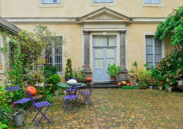 Drzwi wejściowe ozdobione jesiennymi kwiatami, dyniami i roślinami.