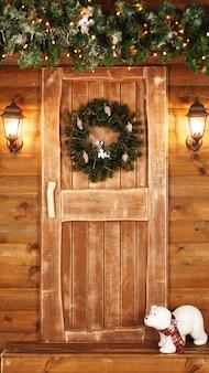 Drzwi wejściowe udekorowane na święta. drewniana bajkowa chata na boże narodzenie