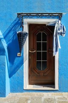 Drzwi z parasolem na niebieskiej elewacji domu. włochy, wenecja, wyspa burano.