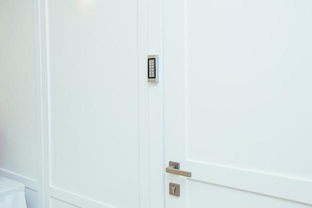 Drzwi z zamkiem szyfrowym na środku pokoju w kolorze białym