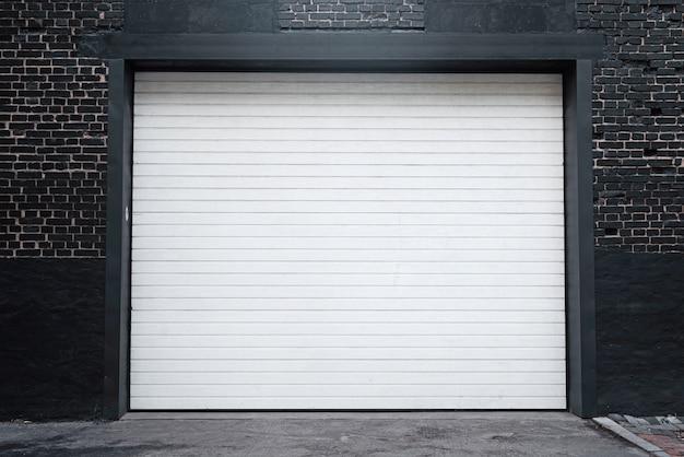 Drzwi żaluzji lub bramy rolowane i betonowa podłoga na zewnątrz