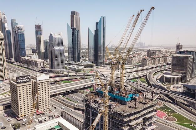 Dubaj, zjednoczone emiraty arabskie, marzec 2019 - widok z lotu ptaka na budynek w budowie na tle drapaczy chmur
