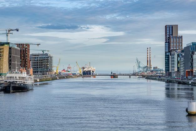 Dublin / irlandia - ujście rzeki liffey od mostu samuela becketta z miejscami budowy wzdłuż uderzeń rzeki.
