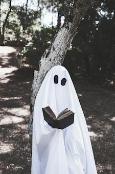 Duch stoi przy drzewną i czytelniczą książką