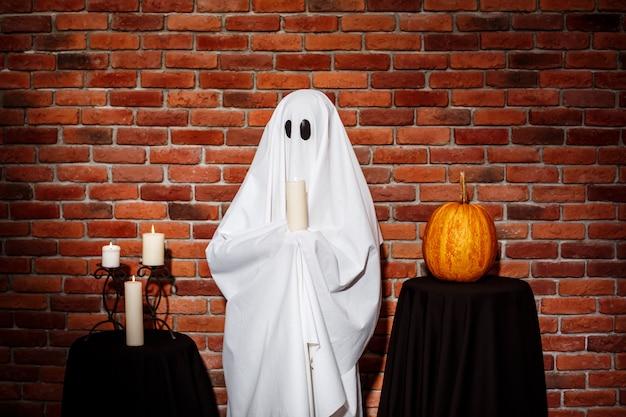 Duch trzyma świeczkę nad ściana z cegieł. impreza halloween'owa.