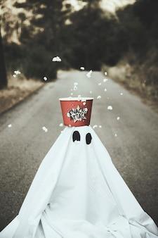 Duch z pudełkiem popcornu na głowie i sypiącymi ziarnami