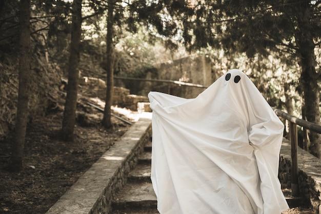 Duch z rozłożonymi rękami na schodach w parku