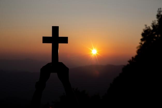 Duchowe modlitewne ręki nad słońcem błyszczą z zamazanym pięknym zmierzchem