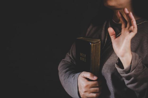 Duchowość i religia, ręce złożone do modlitwy na świętą biblię w kościelnym pojęciu wiary.