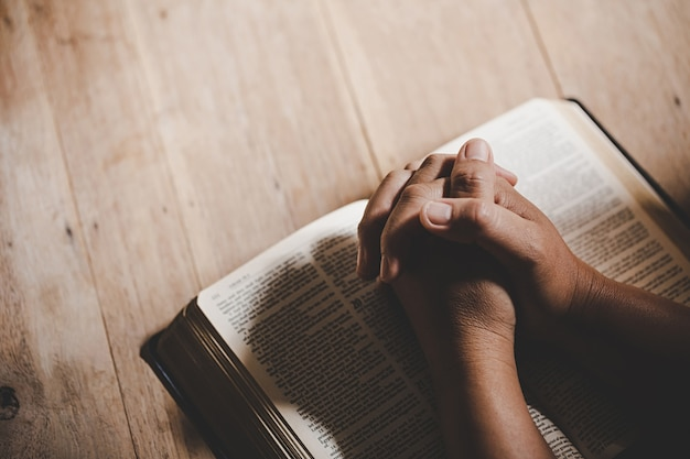 Duchowość i religia, ręce złożone w modlitwie na świętej biblii w koncepcji kościoła dla wiary.