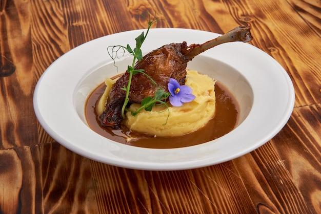 Duck confit pieczone udko kacze z puree na białym talerzu na stole