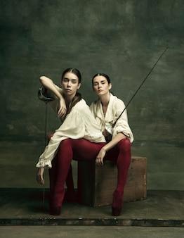 Duet. dwie młode tancerki baletowe jak pojedynki z mieczami na ciemnozielonym tle. kaukaski modele tańczą razem. koncepcja baletu i choreografii współczesnej. kreatywne zdjęcie artystyczne.