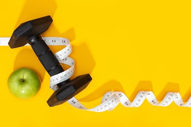 Dumbbells, jabłko i miara taśmy na żółtym tle. zdrowy styl życia lub koncepcja odchudzania. skopiuj miejsce
