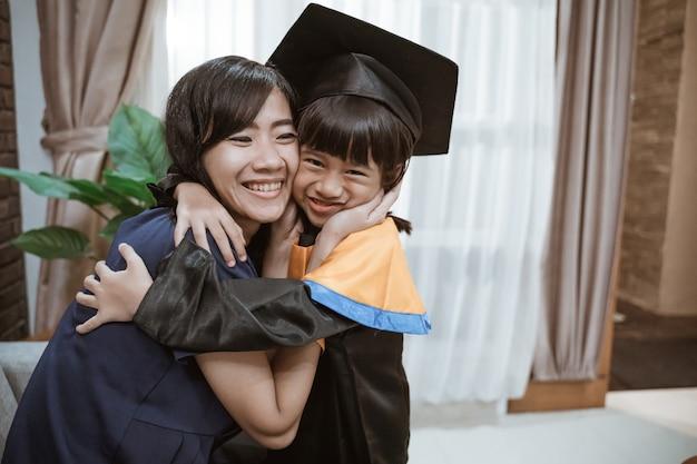 Dumna azjatycka matka obejmuje córkę podczas dnia ukończenia szkoły podstawowej