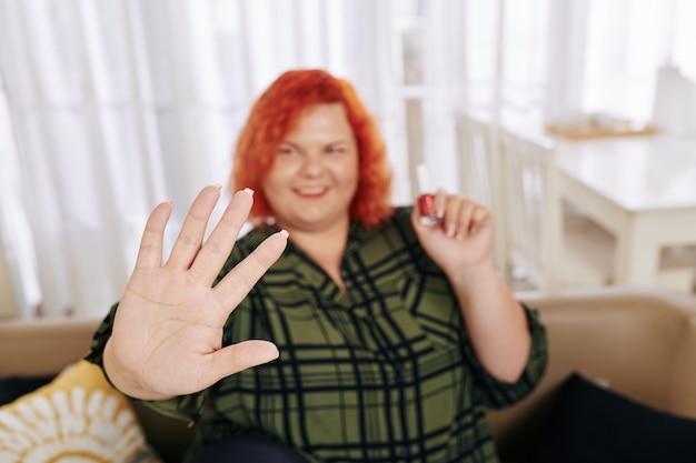Dumna kobieta, patrząc na pomalowane paznokcie