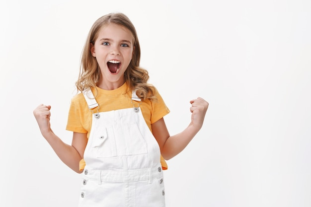 Dumna, ładna młoda, zadowolona dziewczynka o jasnych włosach i niebieskich oczach, gest świętowania pompki pięści, uśmiechnięta radośnie, osiągnięcie sukcesu, triumfowanie z dobrych doskonałych wiadomości, biała ściana