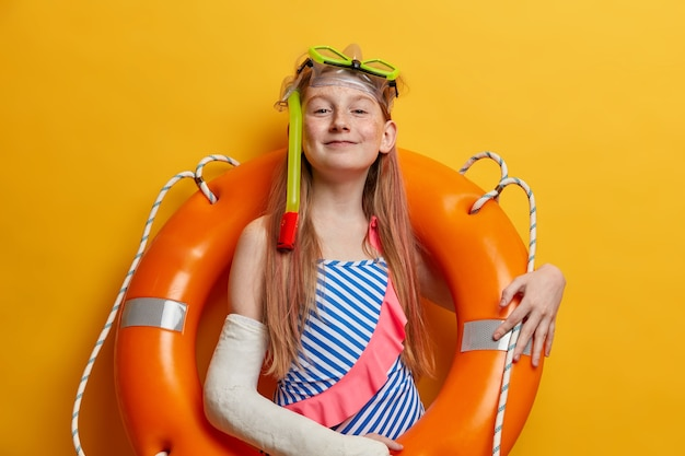 Dumna, zadowolona ruda dziewczyna pozuje w nadmuchanym kole ratunkowym, nosi maskę do nurkowania i strój kąpielowy, lubi pływać w morzu, złamała rękę w gipsie po wypadku, stoi przy żółtej ścianie