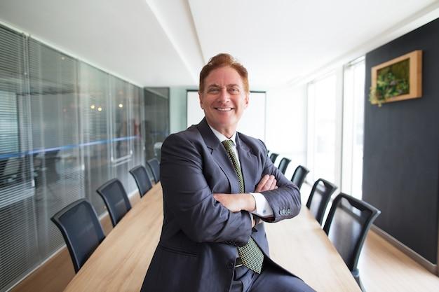 Dumny człowiek biznesowy w średnim wieku w sali konferencyjnej