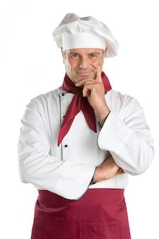 Dumny i zadowolony dojrzały kucharz patrząc na kamery na białym tle