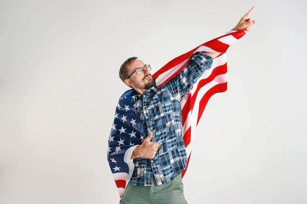Dumny młody człowiek trzyma flagę stanów zjednoczonych ameryki na białym tle na białym studio.