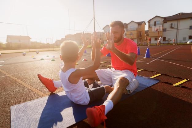 Dumny młody ojciec motywuje swojego małego syna do trenowania z nim.