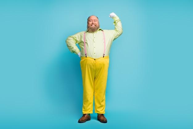 Dumny, nadwymiarowy mężczyzna pokazujący mięśnie na niebieskim tle