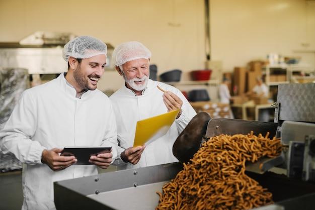 Dumny ojciec i syn w sterylnych ubraniach stojących w swojej fabryce spożywczej i sprawdzających jakość produktów. uśmiechając się i testując swoje produkty.