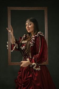 Dumny. portret średniowiecznej młodej kobiety w czerwonej odzieży vintage stojącej na ciemnym tle. modelka jako księżna, osoba królewska. pojęcie porównania epok, nowoczesności, mody, piękna.