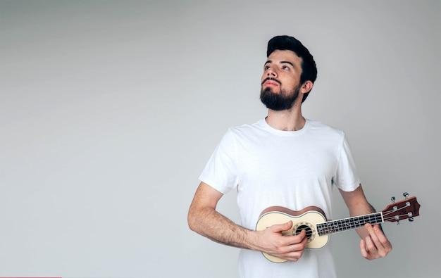 Dumny, poważny, spokojny facet patrzy w górę. trzymaj ukulele w dłoniach i pozuj. samotny muzyk na zdjęciu